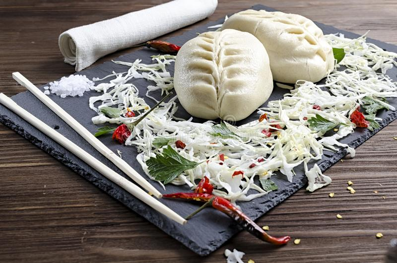 Asian food, Korean pie with cabbage and meat on a slate board, side dish of chopped cabbage, herbs and red pepper, wooden. Background royalty free stock photo