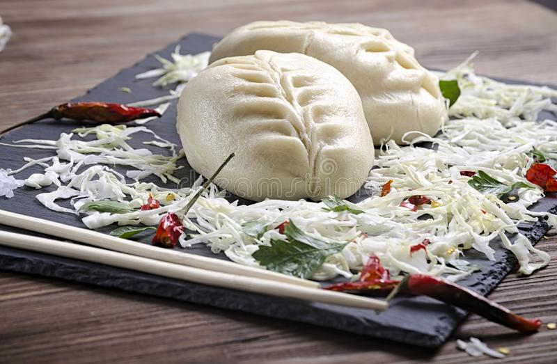Asian food, Korean pie with cabbage and meat on a slate board, side dish of chopped cabbage, herbs and red pepper, wooden. Background stock photos