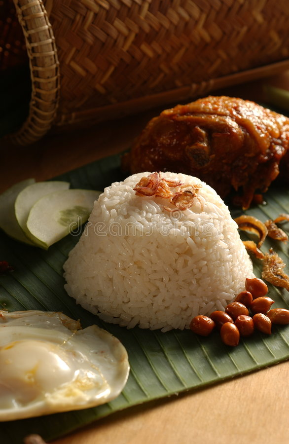 Asian food-Nasi Lemak. An Asian famous and common food, Nasi Lemak usual be serve with fried egg, fried groundnut & dry fishes, cucumbers and fried chicken on stock photography