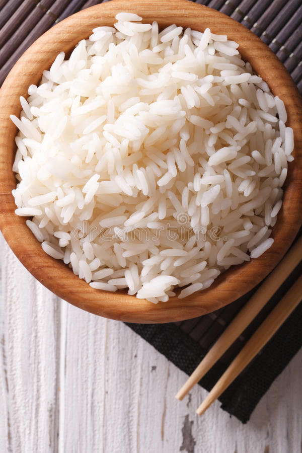 Asian food: rice in a wooden bowl closeup. vertical top view royalty free stock photography