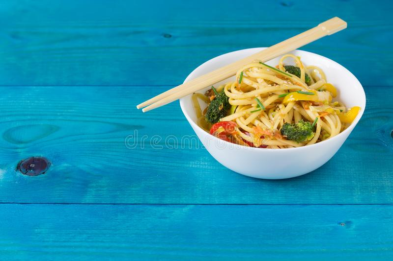 Asian food. Stir fry udon noodles with vegetables on a white bowl, blue wooden backgound, cooked in wok, copy space. Asia food. Stir fry udon noodles with royalty free stock photography