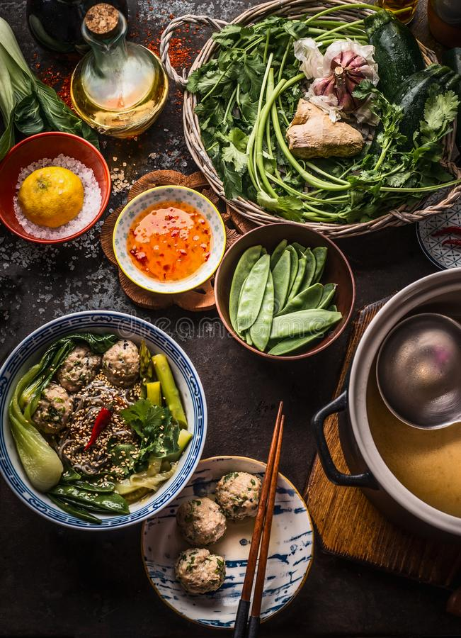 Asian food. Tasty noodle soup with vegetables and meat balls in bowl topped with sesame seeds and chili on rustic kitchen table stock photo