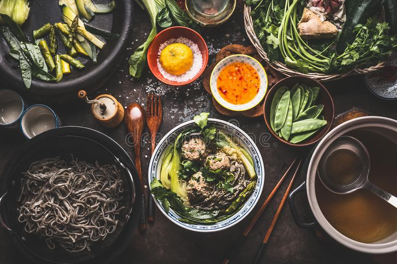 Asian meatballs noodle soup and chopsticks on dark rustic kitchen table with green vegetables ingredients. To view. Asian cuisine. Asian food dishes royalty free stock photography