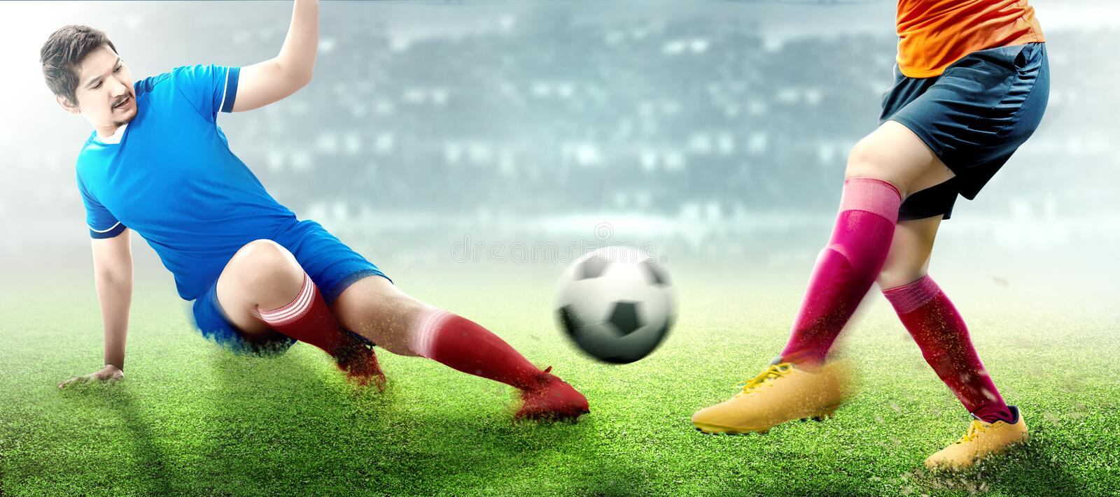 Asian football player man in blue jersey sliding tackle the ball from his opponent. On football field royalty free stock image