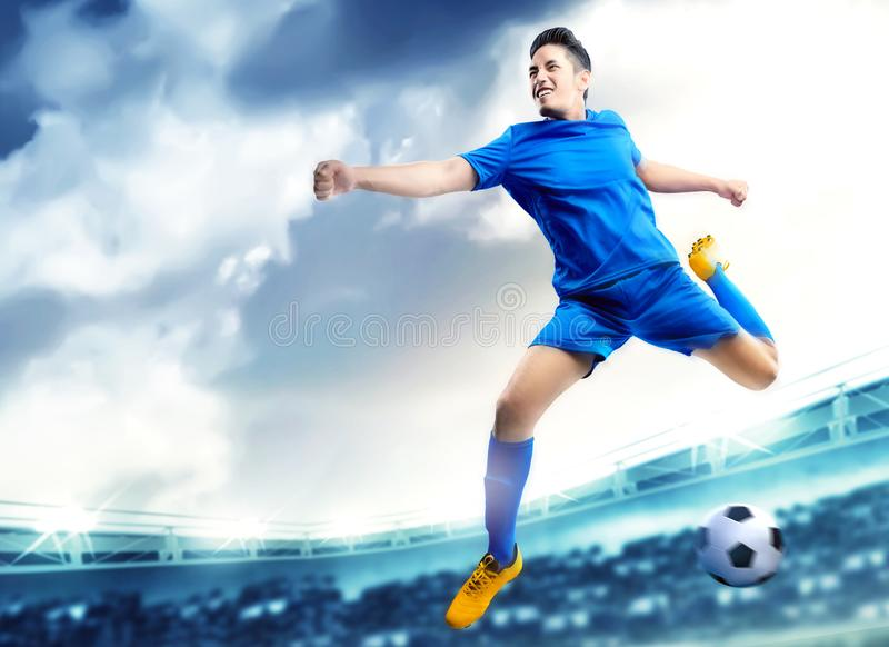 Asian football player man jumping and kicking the ball in the air royalty free stock photography