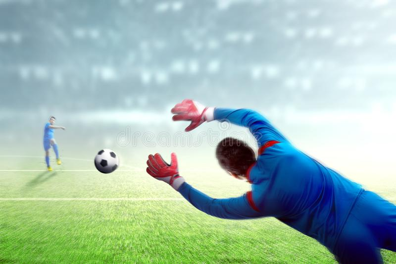 Asian football player man kicking the ball to the goal. On football field at stadium royalty free stock image
