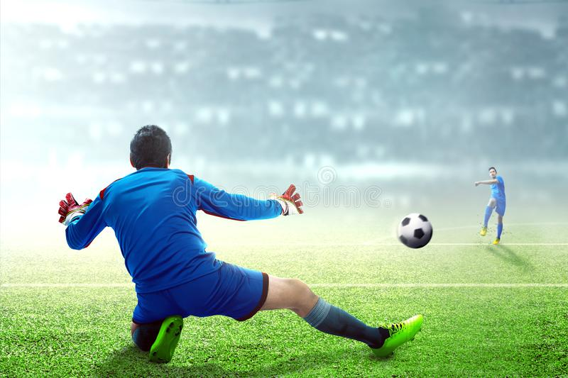 Asian football player man kicking the ball to the goal. On football field at stadium stock photos