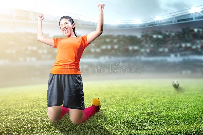 Asian football player woman celebrate her goal with raised arms and kneeling. On the football field at stadium stock photo