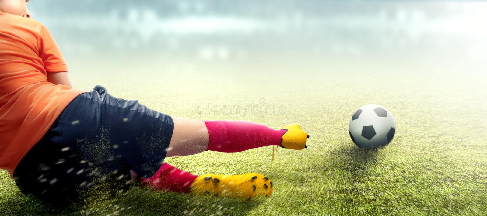Asian football player woman in orange jersey sliding tackle the ball. On the football field royalty free stock photos