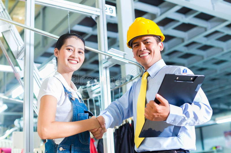 Asian foreman in textile factory giving training royalty free stock images
