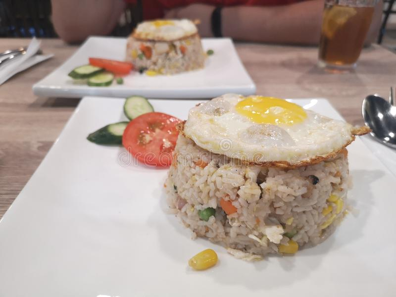 Asian fried rice with vegetables and sunny side up egg stock images