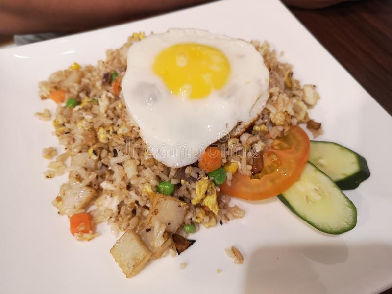 Asian fried rice with vegetables and sunny side up egg 免版税库存图片