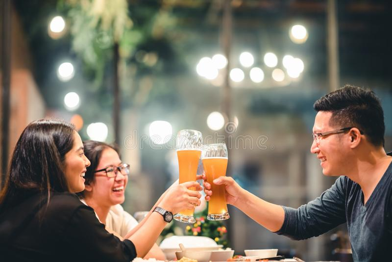Asian friends or coworkers cheering with beer, celebrating together at restaurant or night club. Young people toasting at party. royalty free stock image