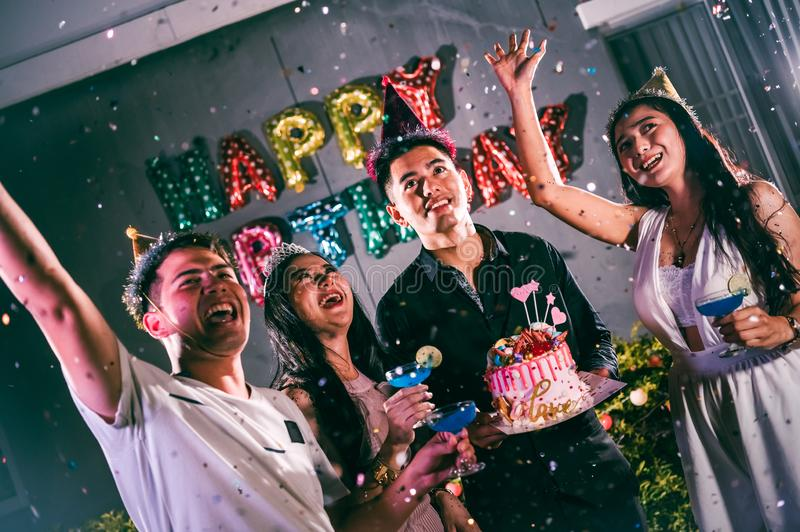 Asian friends having fun in birthday party at night club with birthday cake. Event and anniversary concept. People lifestyles and stock image