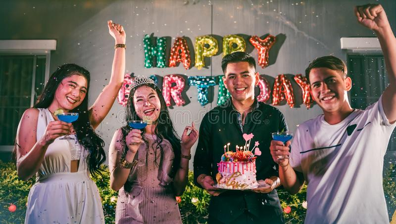 Asian friends having fun in outdoor birthday party at night club with birthday cake. Event and anniversary concept. People stock image