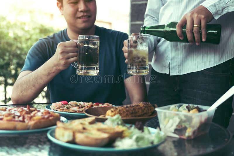 Asian friends are pouring beer into the glass while friends are waiting to celebrate in their home stock photos