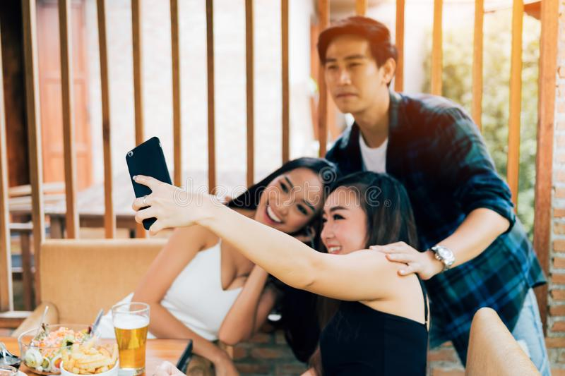 Asian friends smiling and taking selfie in restaurant. royalty free stock photo