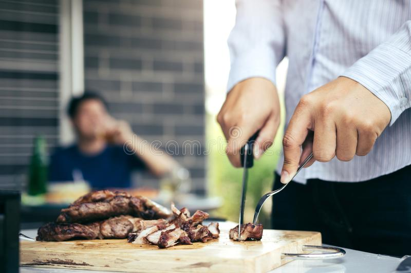 Asian friends are using a knife and a fork to cut the grilled meat on the chopping board to bring food together with friends stock images