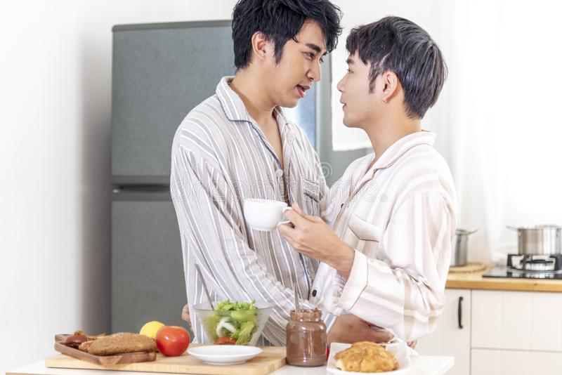 Asian gay couple homosexual cooking together in the kitchen prepare fresh vegetable make organic salad healthy food. Asian people stock photos