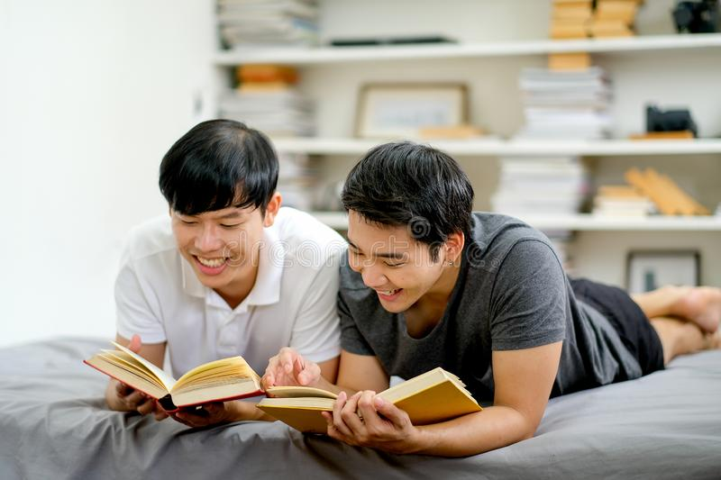 Asian gay couple read some books together in the reading room of their house and they look happy and fun royalty free stock photos