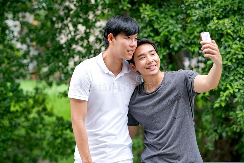 Asian gay couple take photo selfies of themselves together at balcony with green tree background and day light stock photography