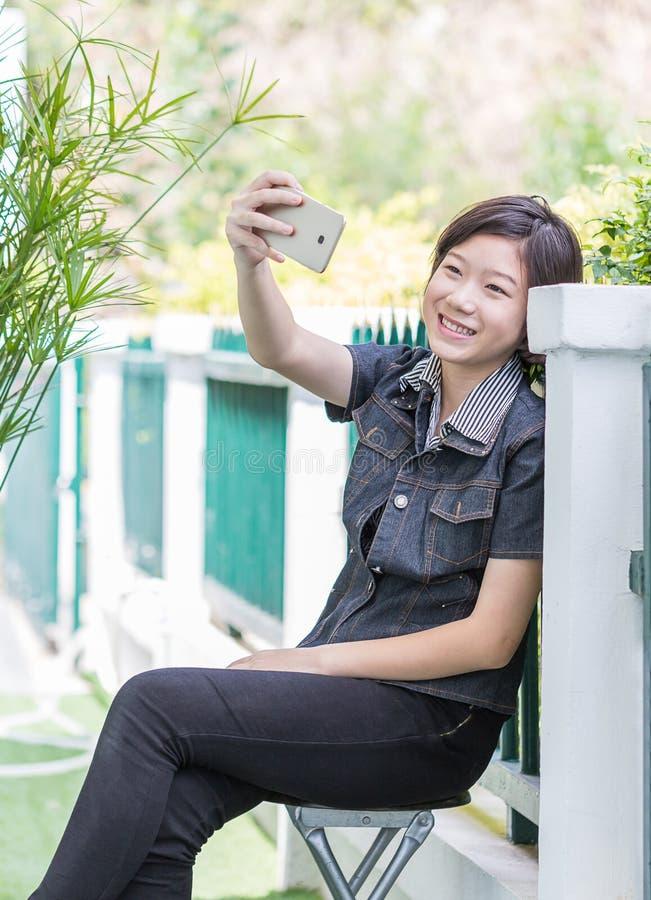 Asian gir makes self-portrait on smartphone royalty free stock photos