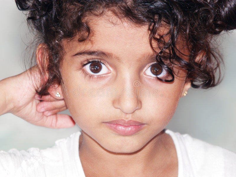 Asian Girl. Closeup portrait of a young Asian girl between the ages of 5-9. Dark curly hair and large brown eyes. Serious expression. Right hand is fisted behind stock images