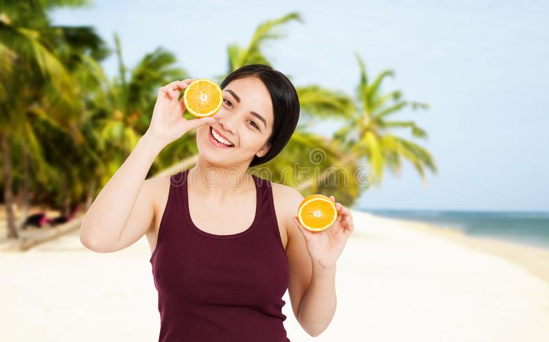 Asian girl with beautiful clear skin is holding fruits on the beach with sea background - health and weight loss concept royalty free stock photos