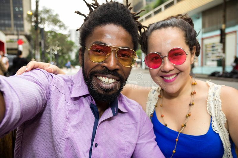 Asian girl and black man dating and having fun in the street. Multiethnic brazilian couple stock photography