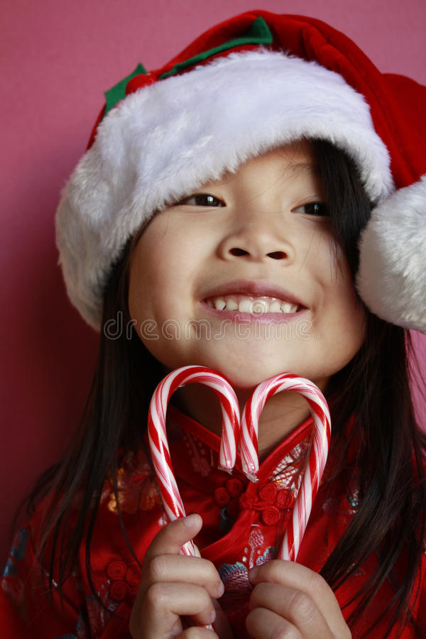 Asian girl with candy canes and santa hat royalty free stock image