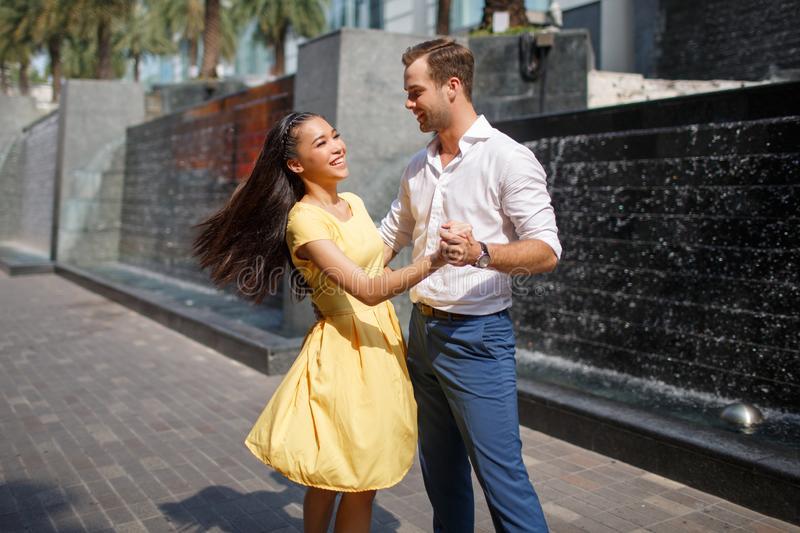Asian girl and caucasian man together dancing on the street royalty free stock photos