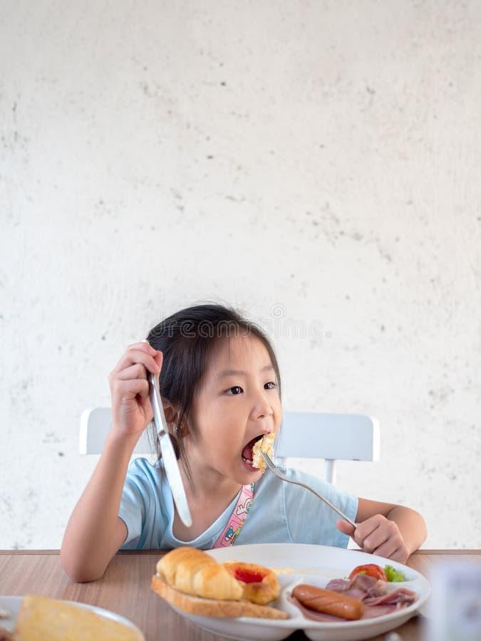 Asian girl child eating american breakfast stock photo
