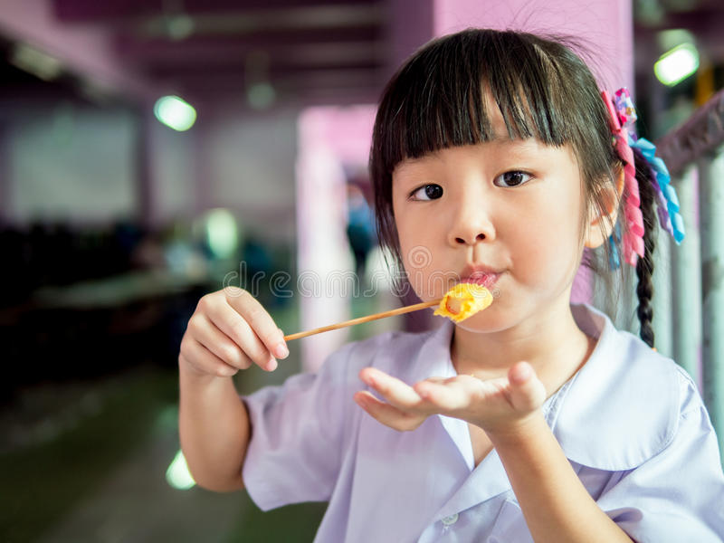 Asian girl child eating a crispy wonton stock photos