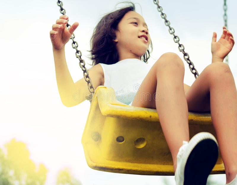 Asian girl children playing on the swing. stock photos