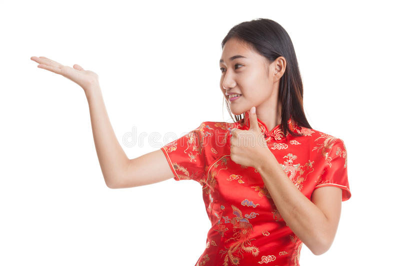 Asian girl in chinese cheongsam dress thumbs up with blank spa. Ce on her hand isolated on white background royalty free stock images