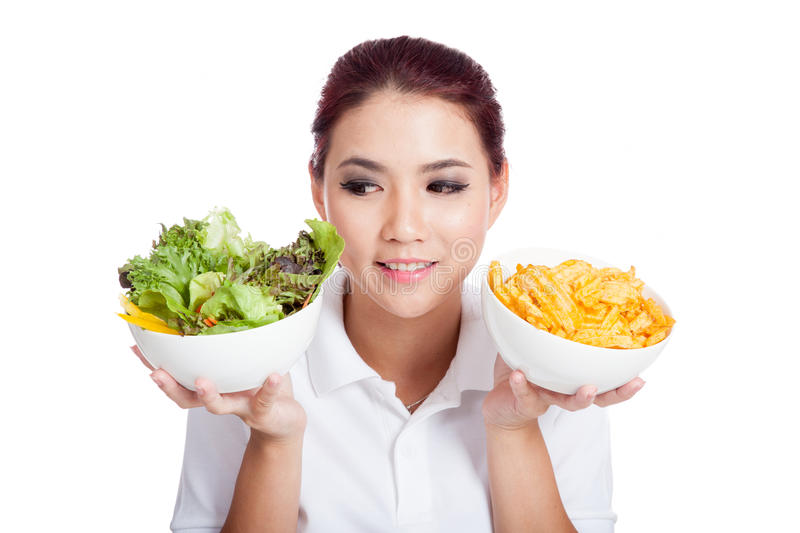 Asian girl choose salad over crisps royalty free stock image