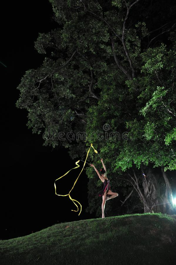 Asian girl dancing ballet under big tree at night. Under the big tree at night, Asian girls dancing ballet, charming night, open-air stage, close to nature stock photo