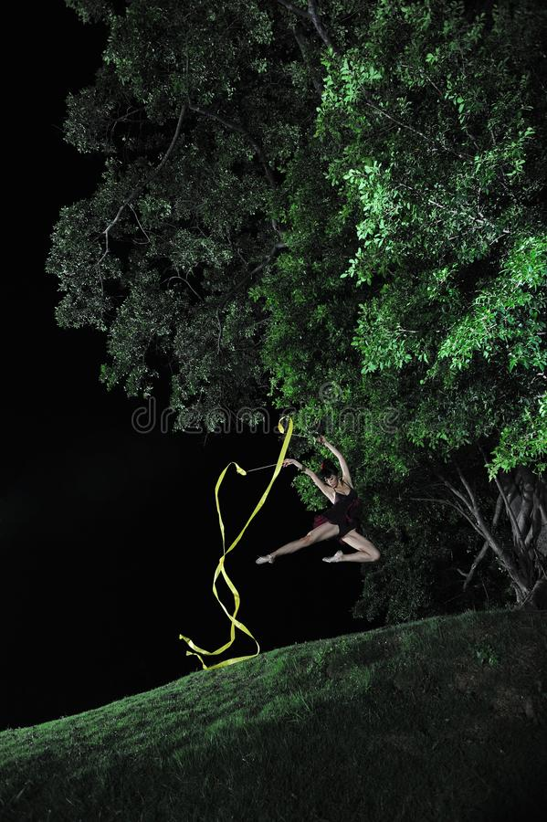 Asian girl dancing ballet under big tree at night. Under the big tree at night, Asian girls dancing ballet, charming night, open-air stage, close to nature royalty free stock images
