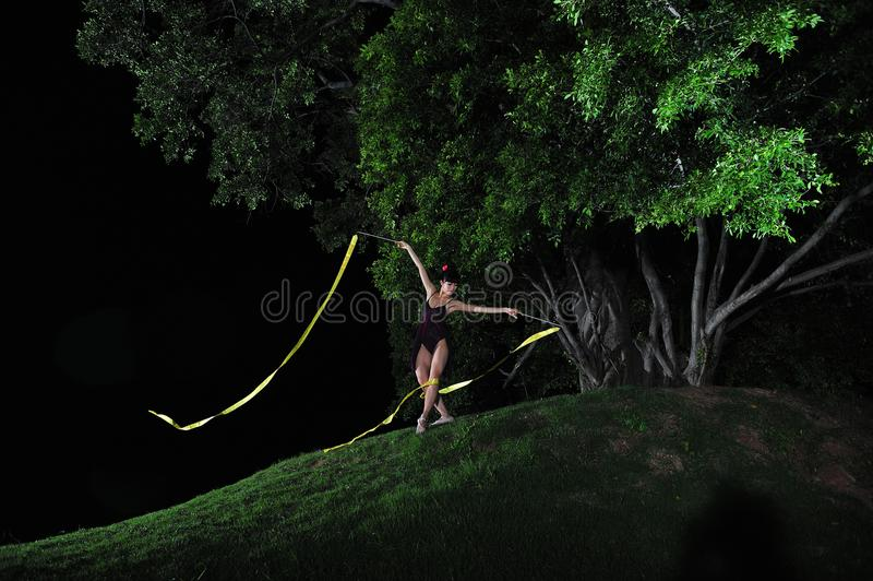 Asian girl dancing ballet under big tree at night. Under the big tree at night, Asian girls dancing ballet, charming night, open-air stage, close to nature stock image