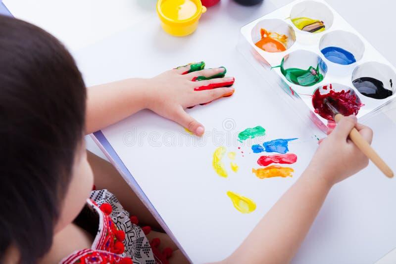 Asian girl doing fingerprints using drawing tools, art education. Little asian (thai) girl doing fingerprints using multicolored drawing tools (watercolor paints stock photo