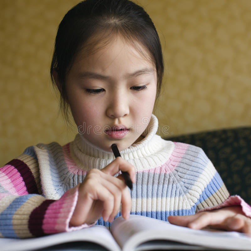 Asian girl doing homework royalty free stock photos
