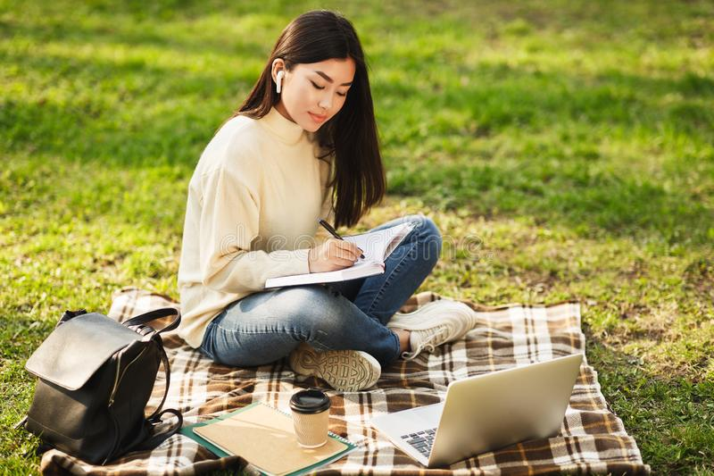 Asian girl doing homework, writing notes and using laptop. In university campus stock photos