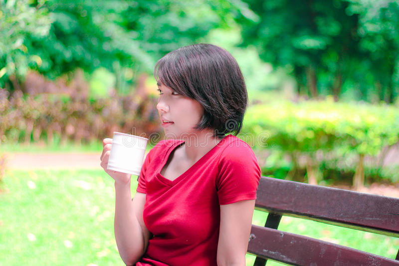 Asian girl drinking coffee and smile in the garden stock photos