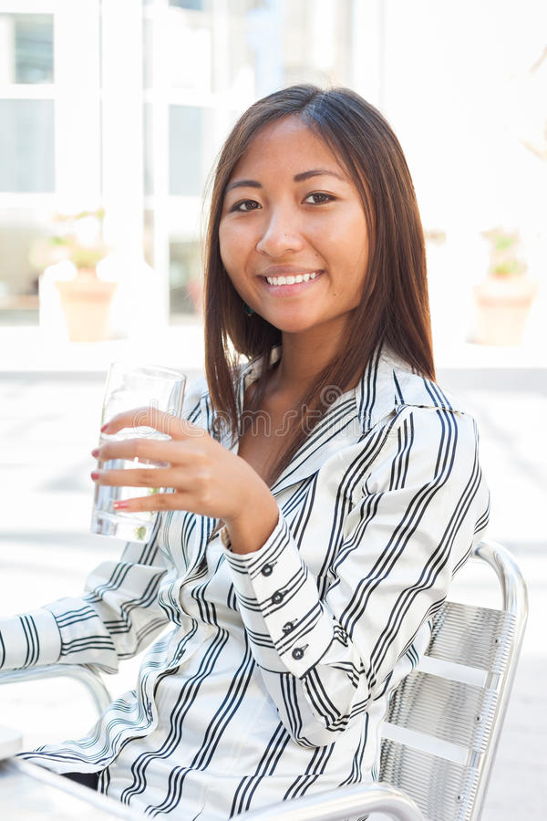 Asian girl drinking a glass of water. Portrait of an smiling asian girl drinking a glass of water royalty free stock photos