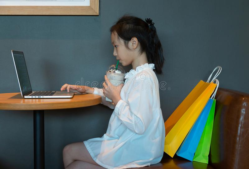 Asian girl drinking while keyboarding a new article using lapto stock photos