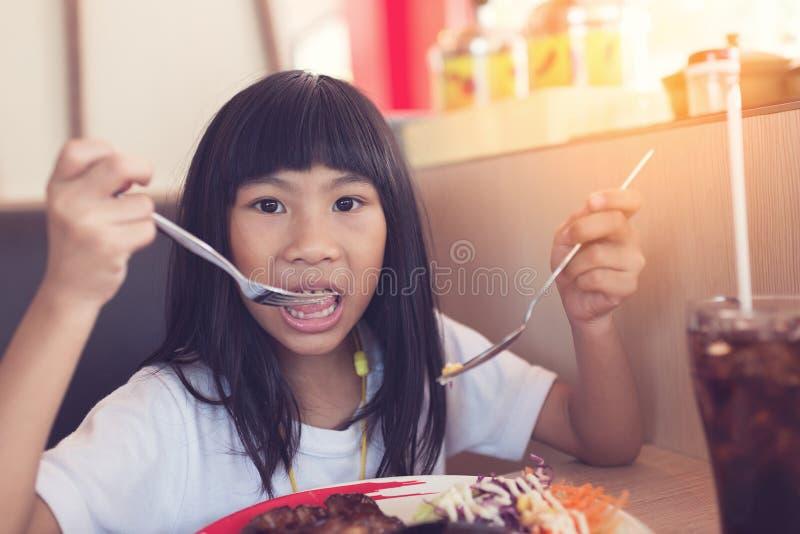 Asian girl eating chicken steak in restaurant.. royalty free stock photo