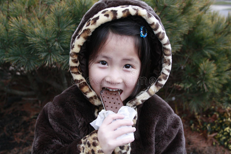 Asian girl eating ice cream with coat on. Little asian chinese girl with leopard print coat on eating ice cream with her hood on royalty free stock photography