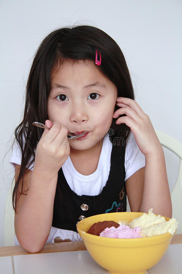 Asian girl eatingbowl of ice cream royalty free stock image