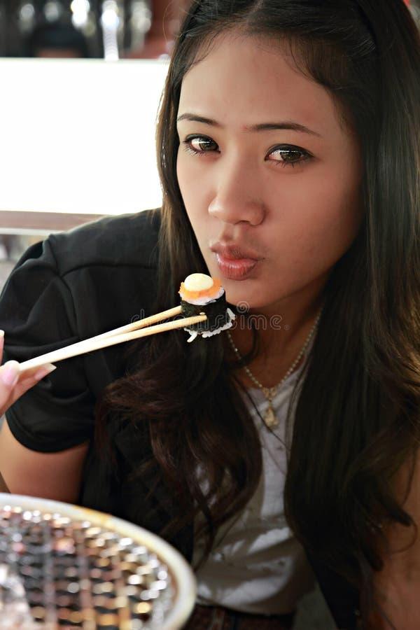 Asian girl enjoying eating sushi rolls stock photos