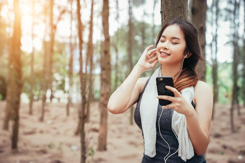 Asian girl is exercising, and drinking cool water and listening music royalty free stock photo